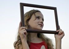 Girl with wooden frame Stock Photography