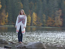 Girl on the wooden jetty at a lake in autumn season.  Stock Photography