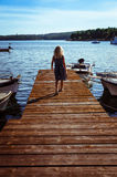 Girl in wooden jetty. Little girl with long blond hair walking in wooden jetty Stock Image