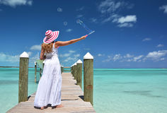 Girl on the wooden jetty making soap bubbles Stock Photos