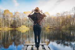 Girl on a wooden old bridge on a lake. Young beautiful girl on a wooden old bridge on a lake in the picturesque autumn forest. Toning Royalty Free Stock Photography