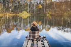 Girl on a wooden old bridge on a lake. Young beautiful girl on a wooden old bridge on a lake in the picturesque autumn forest. Toning Royalty Free Stock Image
