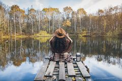 Girl on a wooden old bridge on a lake. Young beautiful girl on a wooden old bridge on a lake in the picturesque autumn forest. Toning Stock Photo