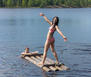 Girl on a wooden raft Stock Photos