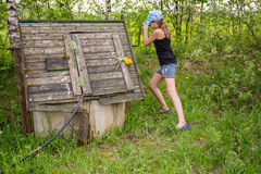 Girl in wooden well Stock Images