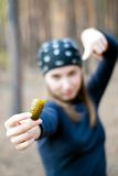 Girl in the woods. With a cucumber in her right hand. focus on cucumber Royalty Free Stock Images