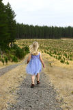 Girl in woods. A little girl walking alone along a path by the forest Stock Images
