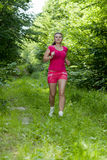 Girl in the woods. Beautiful, young girl jogging in the woods Stock Images