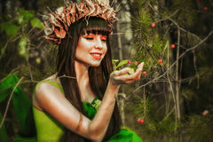 The girl in the woods with berries. The girl touched the berries with your hands in the woods Royalty Free Stock Photo