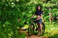 The girl in the woods on a bike Royalty Free Stock Images