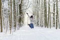 A girl in the woods jumps up. A lot of snow. stock photography