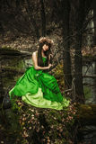 The girl in the woods with a toy. In green dress sitting Royalty Free Stock Photos