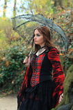 Girl in the woods with umbrella. Beautiful brunette girl with umbrella wearing a red dress standing in the woods Royalty Free Stock Image