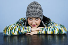 Girl in wool cap sit with head on table Stock Photography
