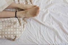 Girl with wool socks, sleeping in bed Stock Image