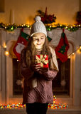 Girl in wool sweater and hat looking inside of glowing present b Royalty Free Stock Image