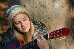 Girl with woolen cap and guitar Royalty Free Stock Images