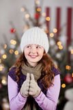 Girl in a woolly cap with a Christmas tree. Pretty young girl in a woolly cap and winter scarf standing n front of a Christmas tree with a thoughtful playful Royalty Free Stock Photo