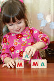 The girl and word mama from cubes Stock Photo