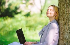 Girl work with laptop in park sit on grass. Natural environment office. Work outdoors benefits. Woman with laptop work. Outdoors lean tree. Minute for relax royalty free stock photo