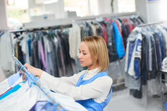 Girl worker hangs Laundry clean clothes on a hanger. In the dry cleaner Stock Images