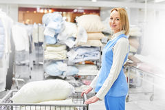 Girl worker holding a Laundry cart with clean pillows Stock Image