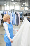Girl worker Laundry looks and checks of white, sheer tulle. At the dry cleaners Stock Image