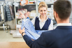 Girl worker Laundry man gives the client clean clothes at the dry cleaners. Male client takes a women Laundry worker clean clothes at the dry cleaners Royalty Free Stock Image