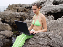 Girl working. A girl working with notebook on the rocks Royalty Free Stock Image