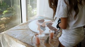 Girl working with acrylic paints in a creative studio, the process of preparing acrylic paints