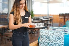 Girl working as waitress holding a tray with tea. The waitress is carrying tea. Hospitable girl waitress holding tray with cup of tea and tea glass teapot for Royalty Free Stock Photo