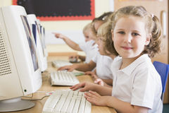 Girl working on a computer at primary school Stock Photos