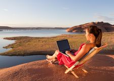 Girl Working on Computer at Sunrise at Lake Powell Royalty Free Stock Photos
