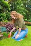 Girl working in garden with grass shears. Young european woman working in garden with grass shears Stock Image