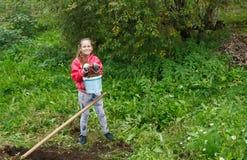 Girl working in garden. Smiling girl teenager in red jacket working in green garden Stock Image