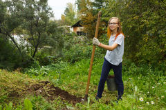 Girl working in garden. Girl teenager with spade and bucket working in garden Royalty Free Stock Photography