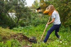 Girl working in garden. Girl teenager working with spade in green garden Royalty Free Stock Image