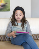 Girl working with her electronic device. An eight year-old Amerasian girl is sitting on a couch with an electronic computer tablet on her lap.  She is engrossed Stock Photos