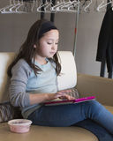 Girl working with her electronic device. An eight year-old Amerasian girl is sitting on a couch with an electronic computer tablet on her lap.  She is engrossed Stock Image