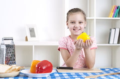 Girl working in the kitchen cutting vegetables Stock Photography