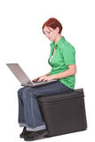 Girl working on laptop. Redheaded girl working on a laptop stock photo
