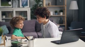 Girl working with laptop then talking with her son and kissing him playing