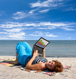 Girl working on laptop near of sea Stock Images