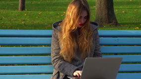 Girl working with laptop outdoors stock footage