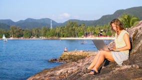 Girl working with laptop sitting at sea coast. Travel. Royalty Free Stock Photo