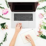 Girl working on laptop and write in diary. Office workspace with female hands, laptop, pink flowers and diary on white table. Top. View royalty free stock photos