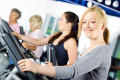 Girl working out at the gym. Attractive young blond girl working out with friends at the gym Royalty Free Stock Photo