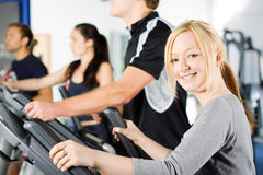 Girl working out at the gym. Attractive young blond girl working out with friends at the gym Stock Photo