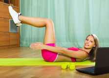 Girl working out with notebook in gym. Active smiling young woman working out with notebook in gym Royalty Free Stock Image