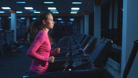 Girl working out in a treadmill at the gym stock footage
